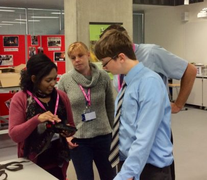 Tenesha showing a camera trap to staff and students