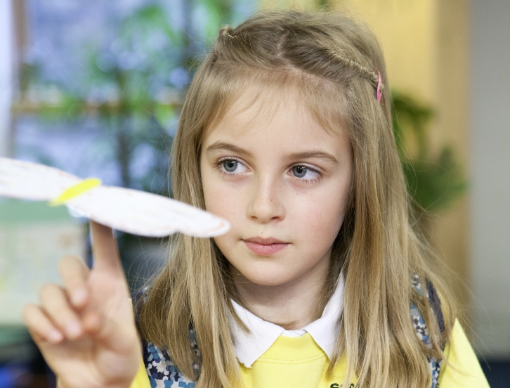 Young girl holding paper aeroplane