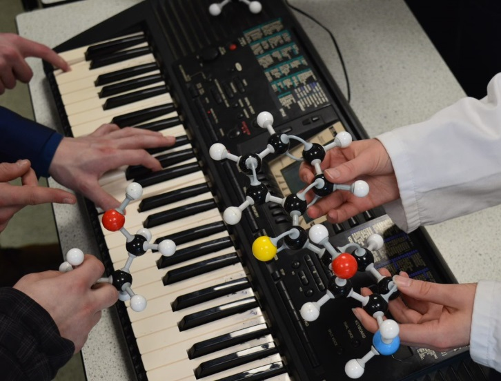 Hands playing the keyboard with other sets of hands holding a molecule in the foreground.