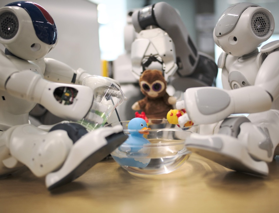Three robots interacting with non-rigid objects including blue and yellow rubber ducks, plushy monkey toy and a glass of water.
