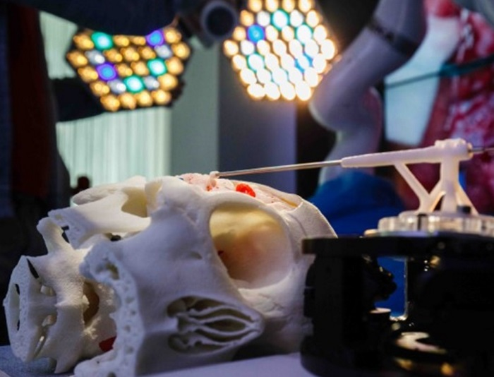 Image shows an operating room with surgical robot operating on a model skull.