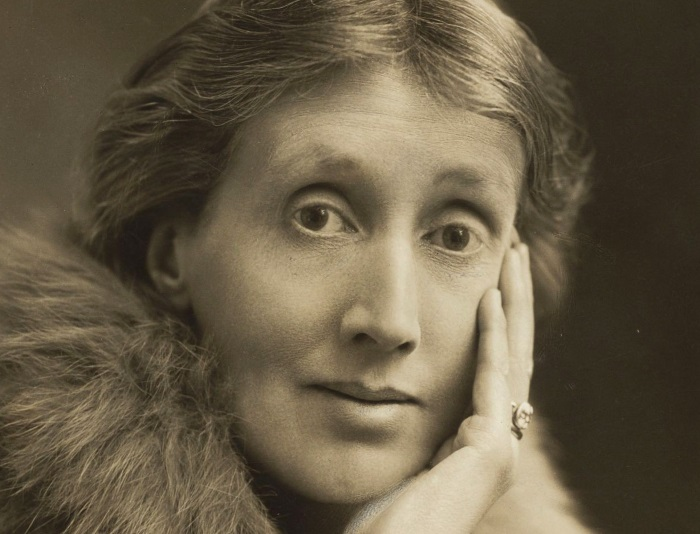Photograph of Virginia Woolfe with her race resting on her hand circa 1927. The photograph is in sepia tones and she wears a fur stole.