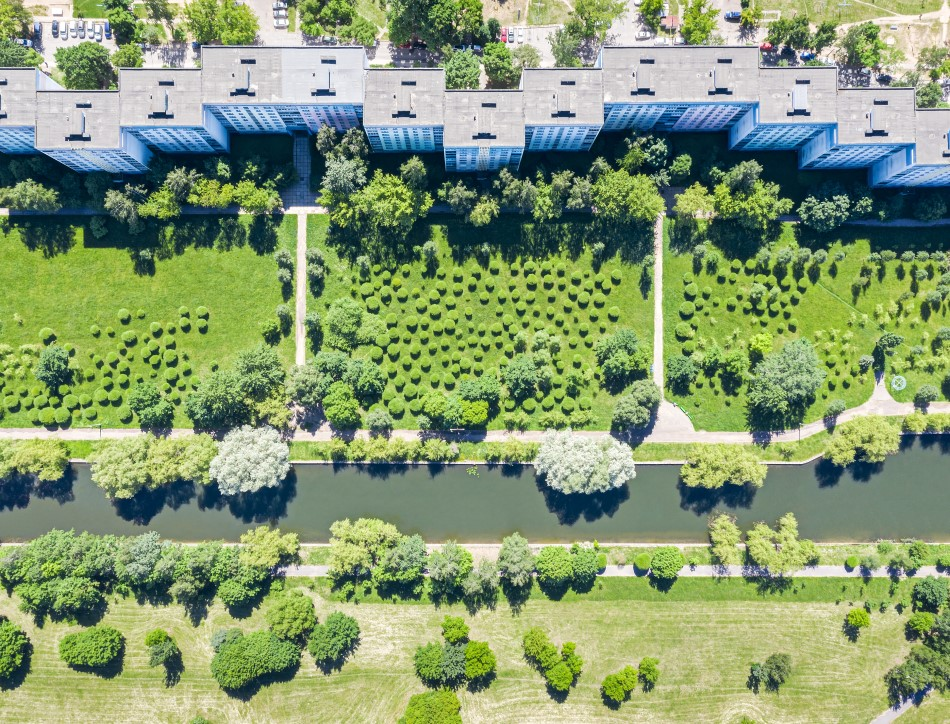 Aerial view of apartment complex next to a green field and river. Image credit: Mr Twister
