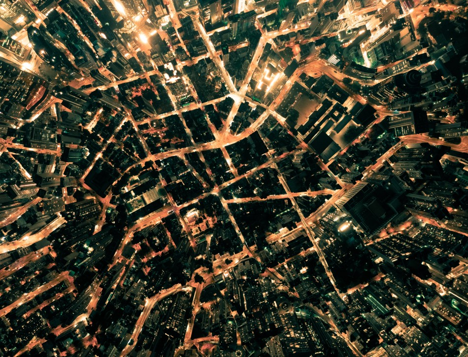 Aerial view of a city at night. Image credit: Chunyip Wong