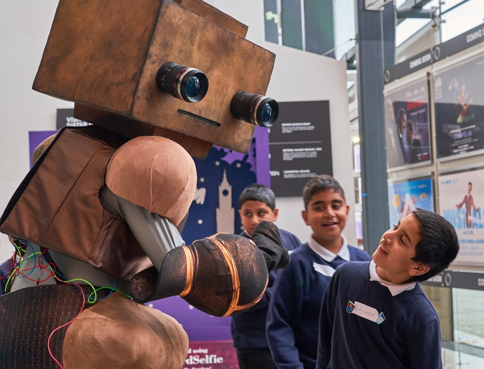Children pose with a robot at the Young People's Book Prize award ceremony in 2019. Image credit: Nathan Buckley