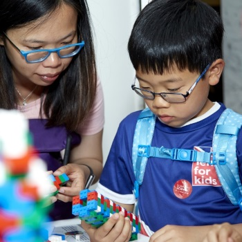 Boy showing a lego structure to a woman