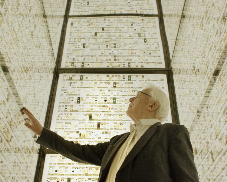 David Attenborough in brightly lit room full of thin section samples