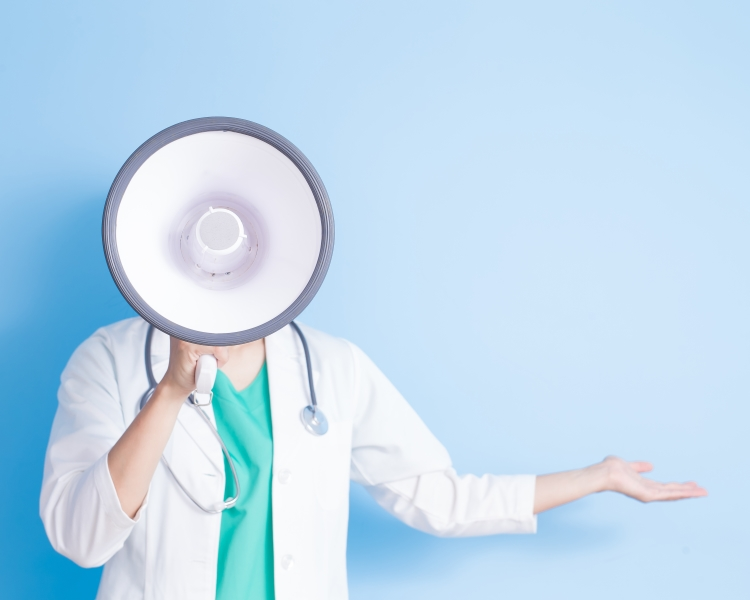 Female doctor in a white lab coat shouting into a megaphone