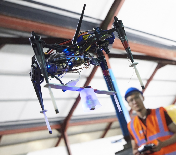 A researcher supervises a drone carrying an inspection sensor flying by itself