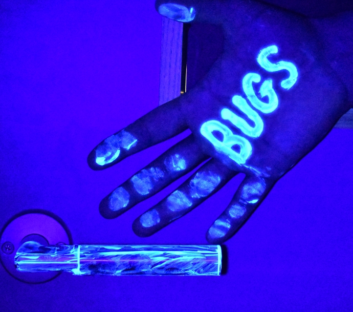 Transmission of bacteria between a person's hand and a door handle demonstrated with UV light.