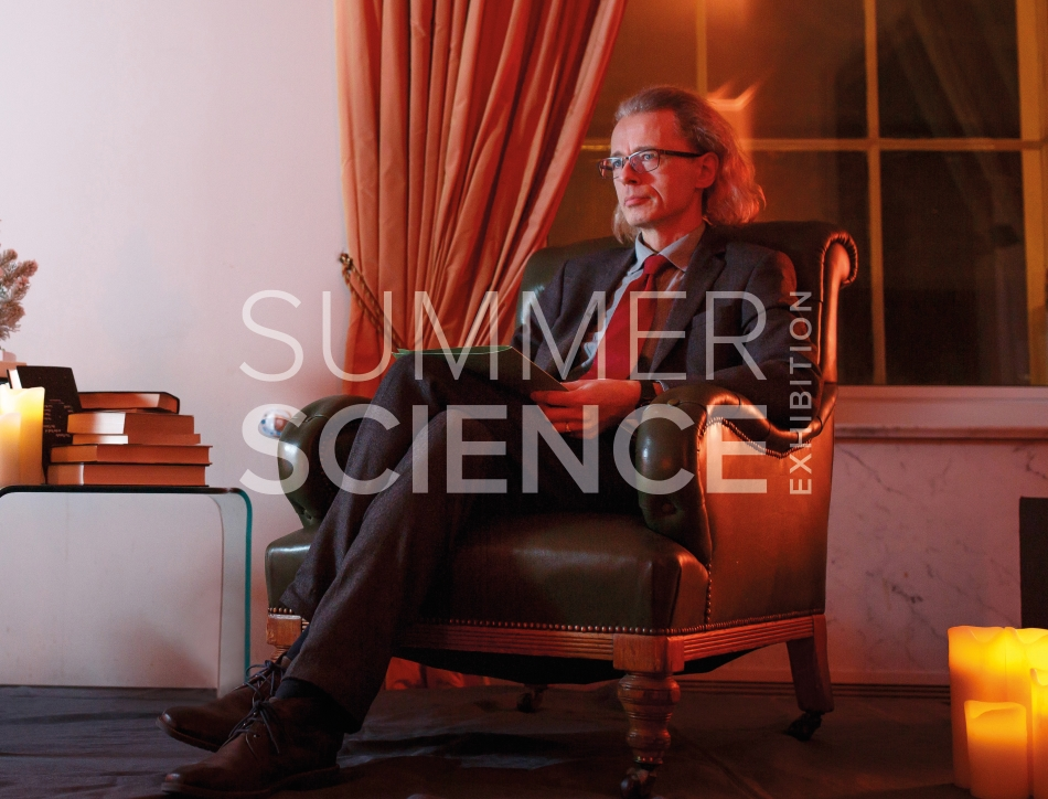 Summer Science Exhibition: man sitting in a room with red lighting, reading a book from the Royal Society's archives