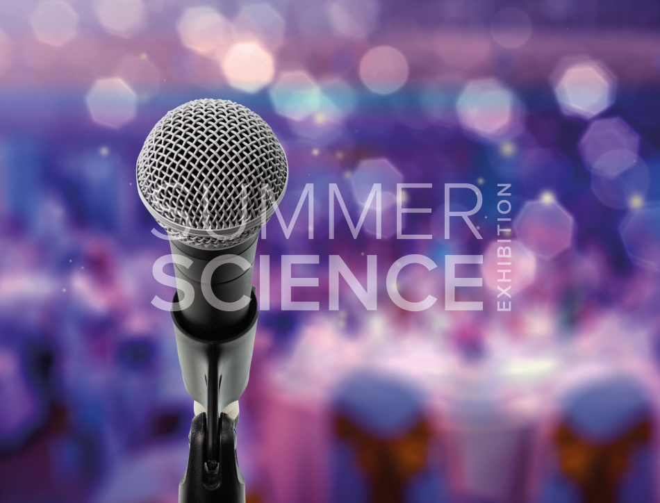 Summer Science Exhibition: a microphone against a blurred background of cabaret tables and lights