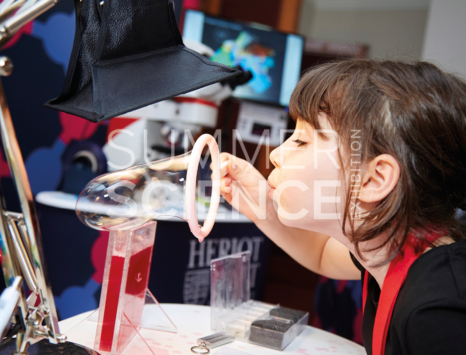 Summer Science Exhibition: a young girl using a bubble blower to blow a giant bubble.