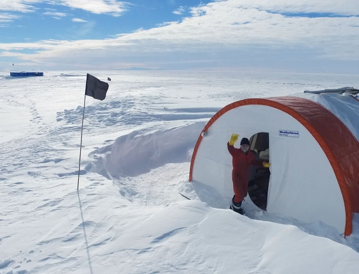 Man waves outside Antarctica tent