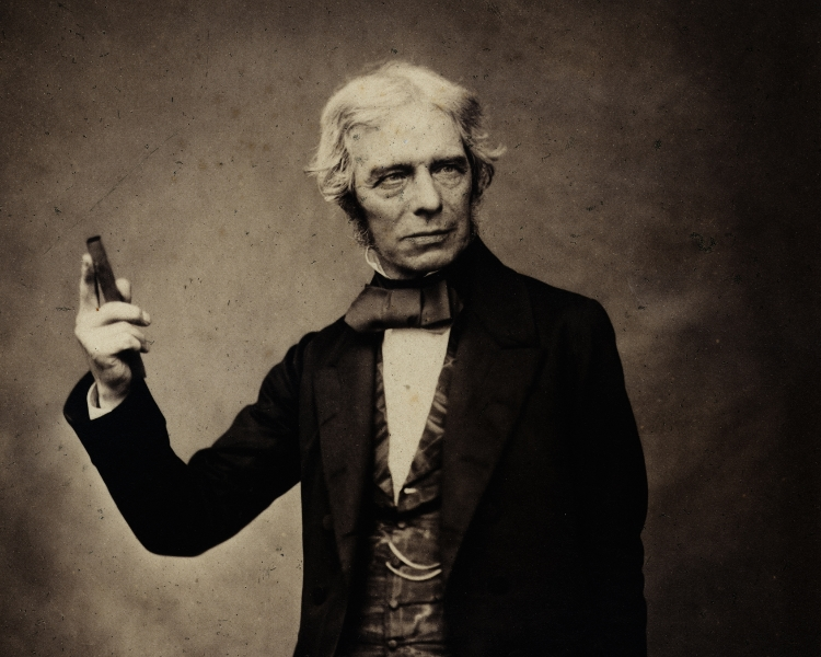 Portrait of Michael Faraday holding a bar magnet