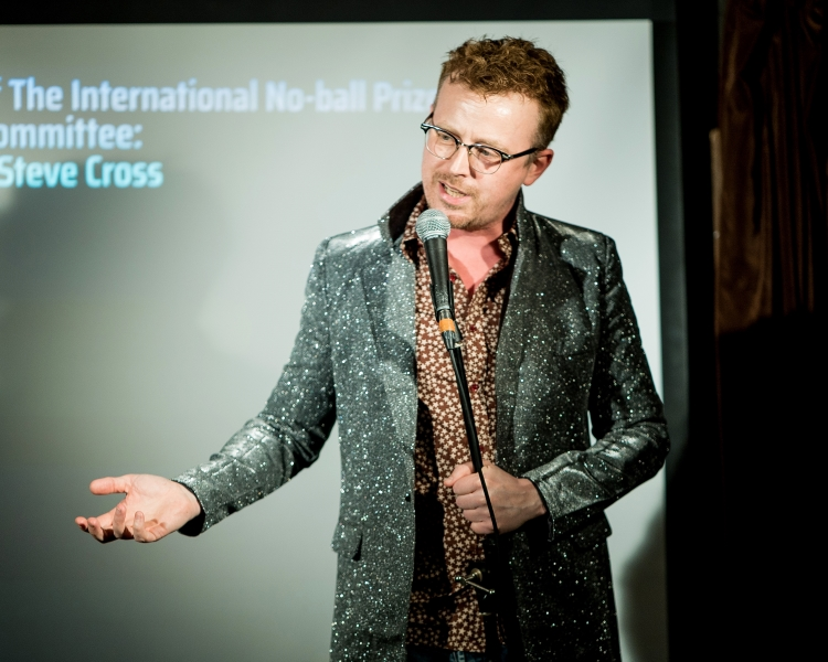 Scientist Dr Steve Cross doing scientific stand up comedy in a silver jacket