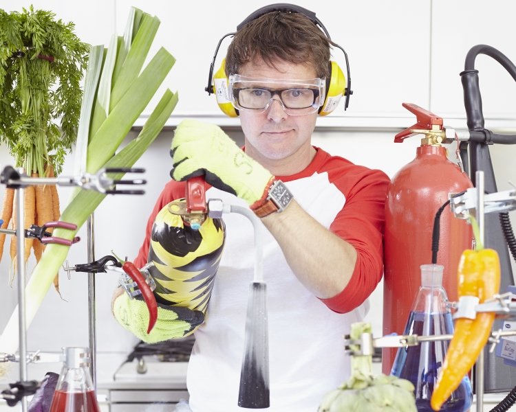 Scientist in a lab holding a fire extinguisher surrounded by vegetables