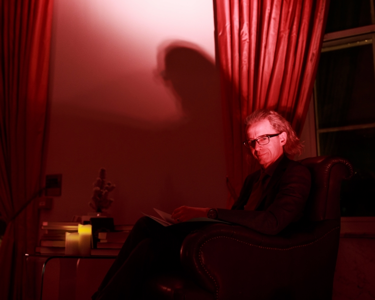 Man sitting in a room with red lighting, reading a book from the Royal Society's archives